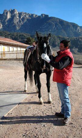 Foto per Uomo che accarezza un cavallo prima di montarlo - Immagine Royalty Free