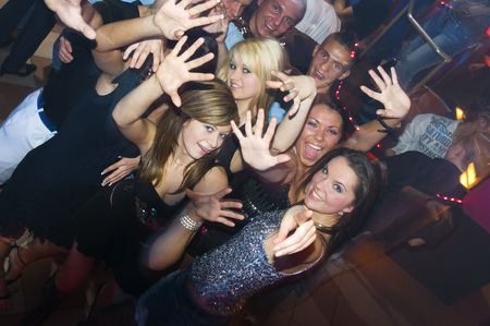 group of young people dancing and enjoying inside a night club