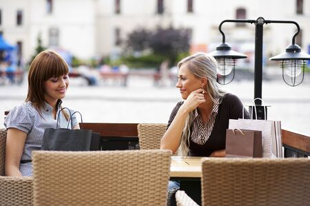 Two beautiful and sophisticated young women friends sitting in a cafe outdoor