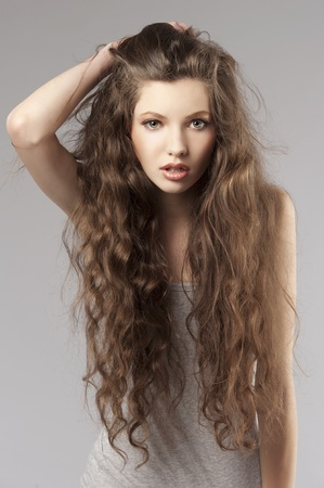 long curly hair young cute girl in a porteait on gray background