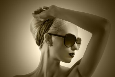 Foto de fashion portrait of young blond woman with hair style black lips and wearing sunglasses posing against white background - Imagen libre de derechos