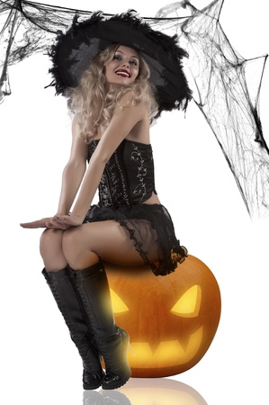 very sexy and attractive blonde dressud up as a witch wearing a black feather hat and sitting on pumpkinの写真素材