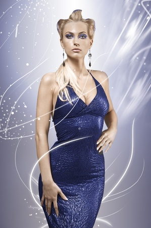 Beauty portrait of an elegant graceful young woman with creative make up and hair style wearing an blue electric dress