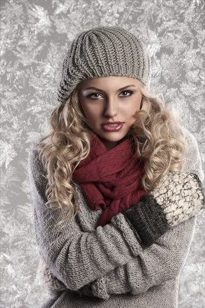 winter fashion shot of a beautiful girl with long curled blonde hair wearing a grey woolen cap, a grey sweater and warm gloves
