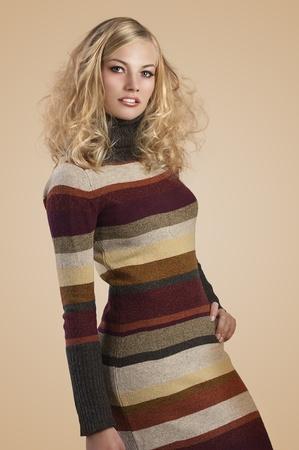 autumn fashion shot of a natural blonde beauty wearing a striped wool dress