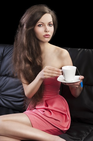 sophisticated young pretty brunette in pink elegant dress sitting on a black sofa and tasting a cup of tea. she looks in to the lens, takes the cup of tea with both hands and her legs are bent on the sofa.