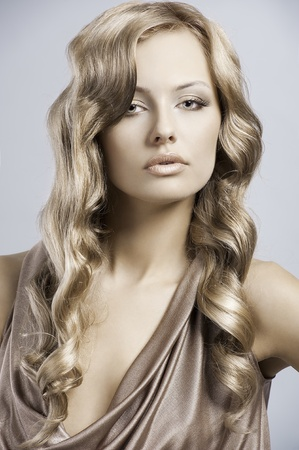 very beautiful and attractive young blond lady in elegant silk dress and with old fashion hair style