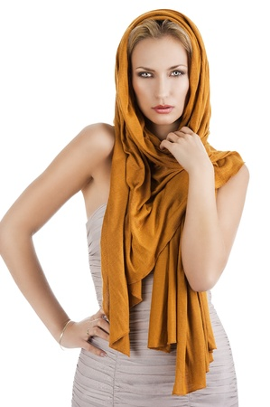 elegant pretty young woman with a long scarf and a lighter dress. She is in front the camera, looks in to the lens. The right hand is on the hip and the left hand is near the neck
