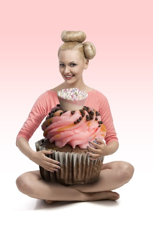 funny portrait of pretty blonde girl with creative hair-style and make-up taking colorful big cupcake in the armsの写真素材