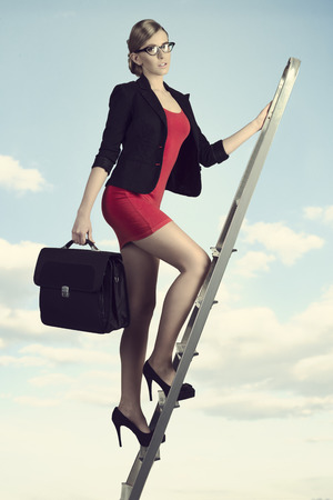 sexy young business woman walking on staircase with short suit and work bag