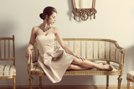 Photo pour interior portrait of brunette elegant girl lying on retro sofa in aristocratic room. Wearing pink dress, precious jewellery and classic hair-style. Luxury atmosphere - image libre de droit