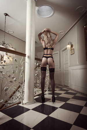 beautiful erotic blond woman showing her sexy backside in black lingerie in sexy pose in luxury ambient