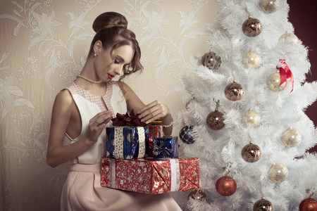 elegant beautiful woman with hair-style sitting near decorated tree with some christmas presents. xmas concept.の写真素材