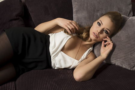 Photo for beautiful woman , in fashion portrait , she is laying on a sofa i her living room , has blond long hair , and looking wth a dream expression in camera - Royalty Free Image