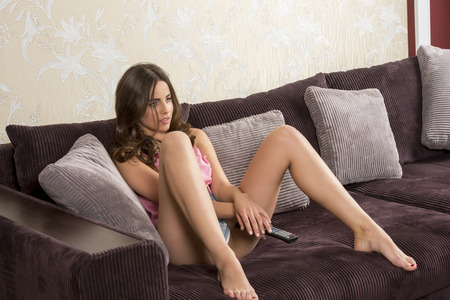 Photo for sexy woman is looking television on comfortable sofa with shorts. She is taking remote control in the hands - Royalty Free Image