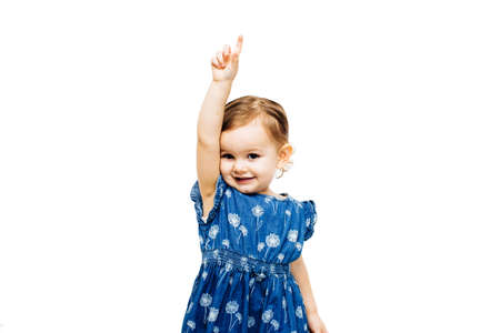 Foto de preschool toddler girl raising hand with index finger pointing up - Imagen libre de derechos