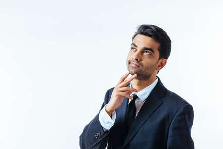 Portrait of a good looking businessman with one finger on his chin. isolated on white background