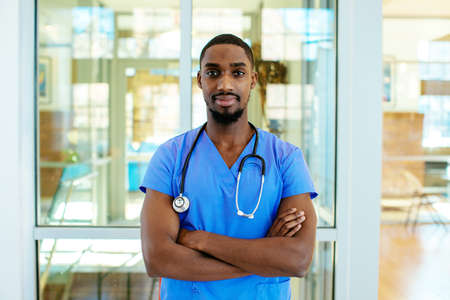 Foto de Portrait of a serious young male doctor or nurse wearing blue scrubs uniform and stethoscope, with arms crossed in hospital - Imagen libre de derechos