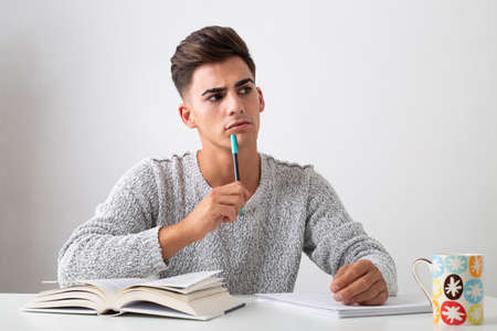 Photo pour serious teenager studying on a desk. On the table there is a book, papers, a pen and a cup. He look thoughtful. - image libre de droit