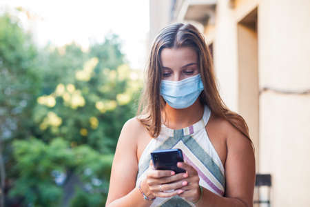 Photo pour Beautiful woman wearing protective mask using a smart phone from her terrace - image libre de droit