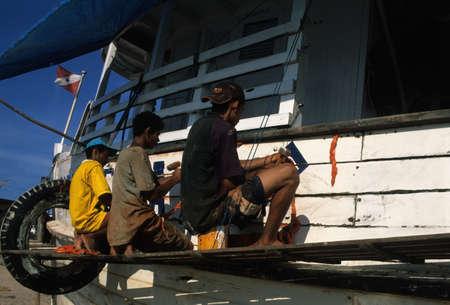 Boys repairing boat on the Amazon River.Montealegre (Amazonas) BRAZIL