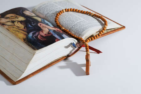 Wooden rosary of Catholic Prayer on an old holy Bible