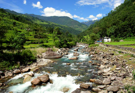 Green rice fields and mountain river landscape, trek to Annapurna Base Camp in Nepal