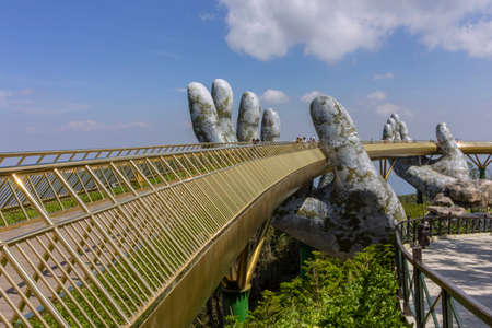 """Da Nang, Vietnam - October 31, 2018: Tourists in Golden Bridge known as """"Hands of God"""", a pedestrian footpath lifted by two giant hands, open in July 2018 at Ba Na Hills in Da Nang, Vietnam."""