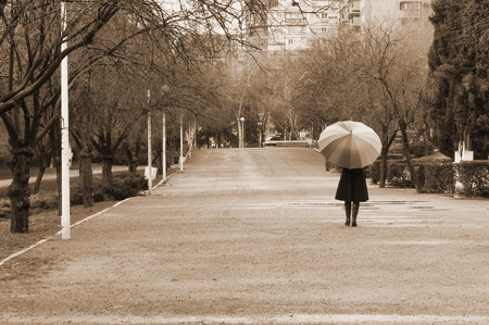Woman walking with umbrella in the park on a rainy day - Sepia