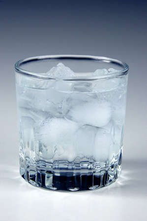 Ice water in a glass with neutral background