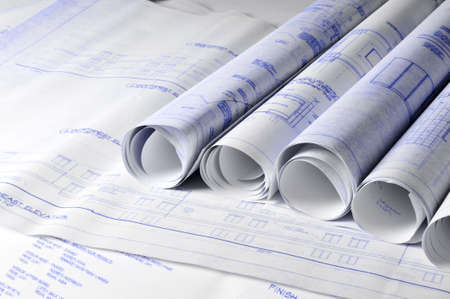 Rolls of architectural blueprins on a drawing table