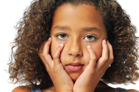 Portrait of beautiful biracial girl with hands on her face
