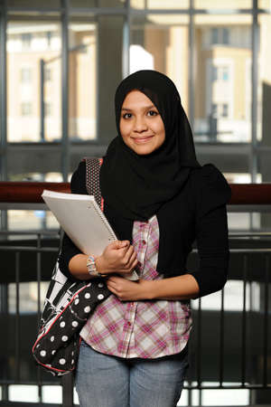 Photo pour Young Arab Student holding a copybook and wearing her traditional veil - image libre de droit