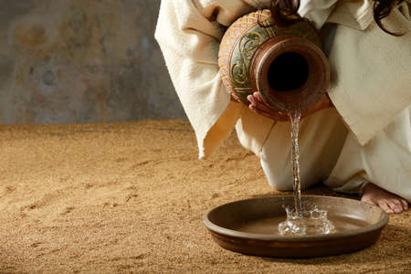 Photo for Jesus pouring water from a jar before the feet washing - Royalty Free Image