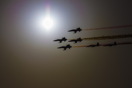 Turkish acrobatic aviation squadron flying over Izmir (Turkey). Backlit image against the sun