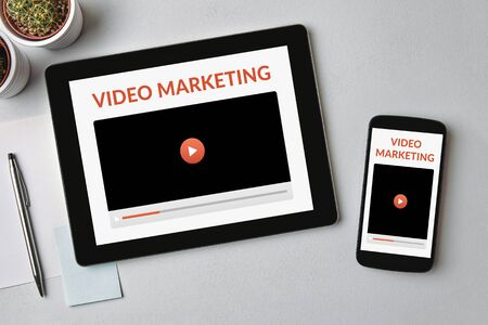 Photo pour Video marketing concept on tablet and smartphone screen over gray table. Top view - image libre de droit