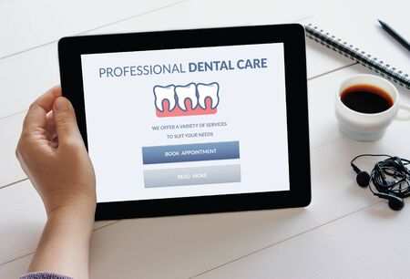 Foto de Hand holding digital tablet computer with dental care concept on screen. - Imagen libre de derechos