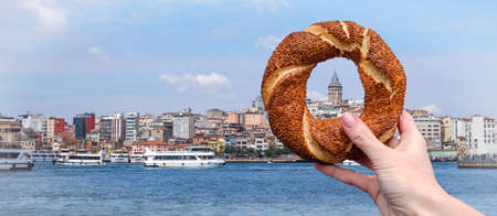 Photo for Traditional Turkish bagel simit in a female hand on the background of the panorama of Istanbul and the Galata Tower, horizontal banner - Royalty Free Image