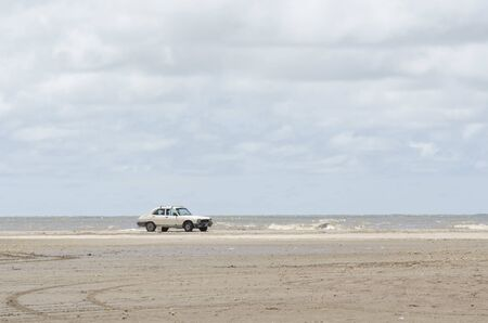 Foto de Beach landscape, a car standing in the sand with the sea in the background, in Punta Rasa, Province of Buenos Aires, Argentina - Imagen libre de derechos