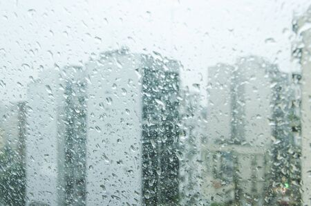 Buildings seen through a glass window full of water droplets a rainy autumnal afternoon in Buenos Aires