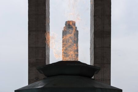Tower of the National Flag Memorial seen through the fire of the votive flame in Rosario, Argentina
