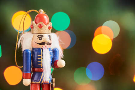 Photo pour Traditional colorful wooden Christmas nutcracker with a green background with colored lights out of focus, copy space - image libre de droit