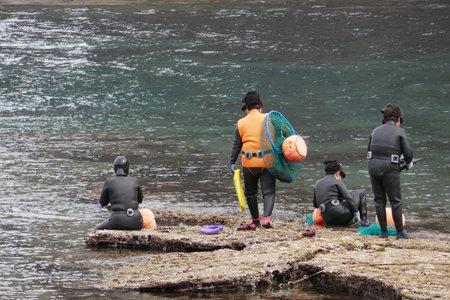 Foto de Jeju Island, South Korea - April 16, 2018 : Haenyo divers prepare to dive to harvest seafood. They can hold their breath for 2 minutes and go 20 meters deep. - Imagen libre de derechos