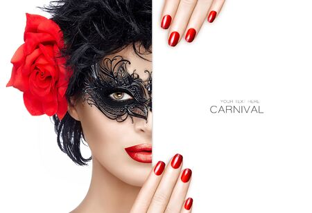 Front close up view on beautiful woman in short black hair, carnival mask and large rose holding blank card near face. Red lips and manicure. Glamorous beauty model wearing creative masquerade eye makeup.