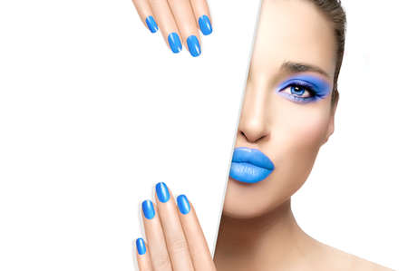 Photo pour Beauty Makeup and Nail Art Concept. Beautiful fashion model girl with blue makeup, perfect skin and trendy cyan nails, half face with a white card template. High fashion portrait isolated on white - image libre de droit