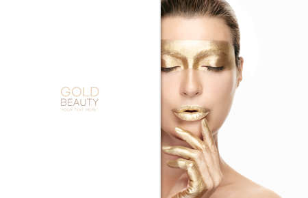 Photo pour Gold based anti aging skincare concept. Beautiful model woman with gold treatment on a flawless skin posing with closed eyes and a serene expression. Close up beauty portrait isolated on white - image libre de droit