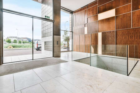 Foto de Contemporary interior design of spacious hall with large windows and light marble floor and with geometric wooden wall decor - Imagen libre de derechos