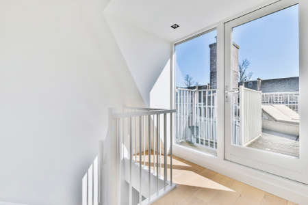 Photo for House storey with wooden floor and glass door to sunny terrace with fence - Royalty Free Image