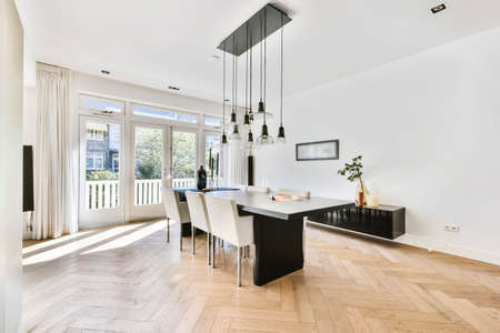 Foto de Stylish interior with parquet floor and contemporary minimalist furniture of dining table and chairs under pendant lamps - Imagen libre de derechos