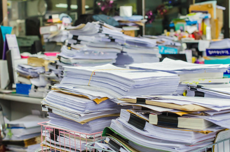 Foto de Pile of documents on desk stack up high waiting to be managed. - Imagen libre de derechos